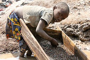 A child in DRC sifts through broken rocks to find copper.